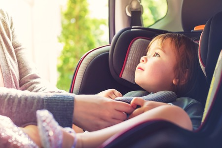 Photo pour Toddler girl buckled into her car seat - image libre de droit