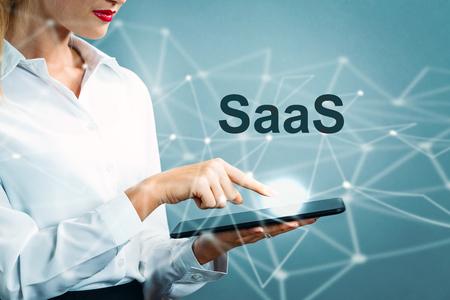 Foto de SaaS text with business woman using a tablet - Imagen libre de derechos