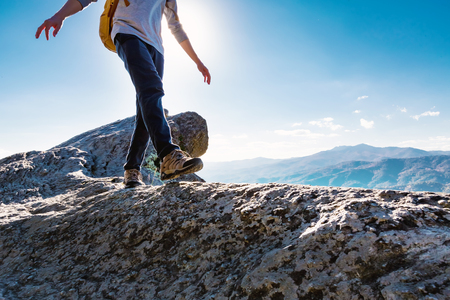 Photo pour Man walking on the edge of a cliff high above the mountains - image libre de droit