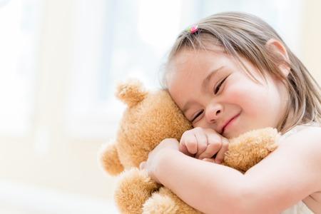 Photo pour Little girl with teddy bear at home - image libre de droit