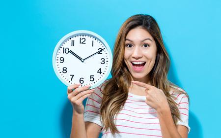 Photo pour Young woman holding a clock on a blue background - image libre de droit