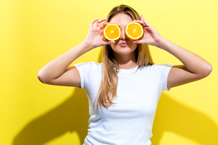 Photo pour Happy young woman holding oranges halves on a yellow background - image libre de droit
