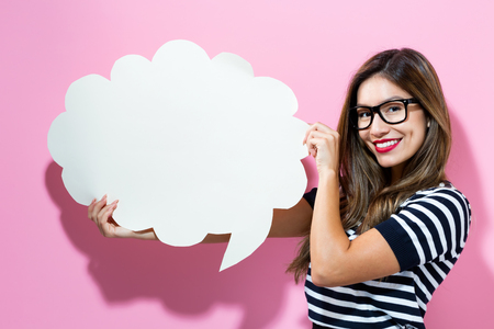 Foto de Young woman holding a speech bubble on a pink background - Imagen libre de derechos