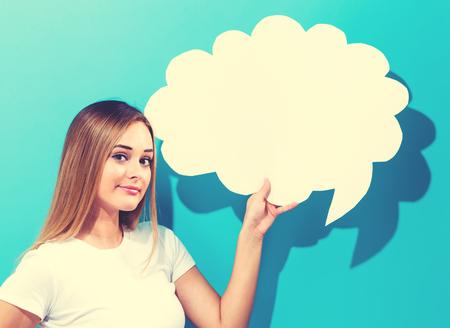 Photo pour Young woman holding a speech bubble on a blue background - image libre de droit
