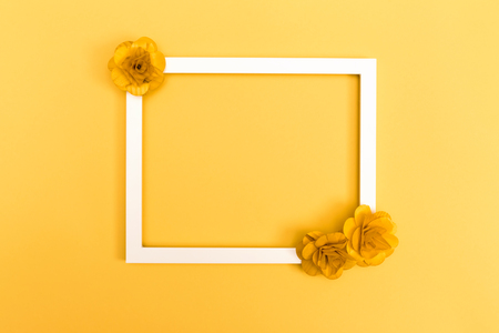 Foto de Picture frame with flowers on a yellow background - Imagen libre de derechos