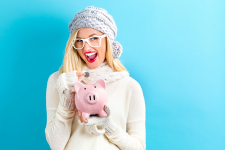 Photo pour Young woman in winter clothes with a piggy bank - image libre de droit
