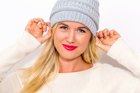 Photo pour Happy young woman in winter clothes on a white background - image libre de droit
