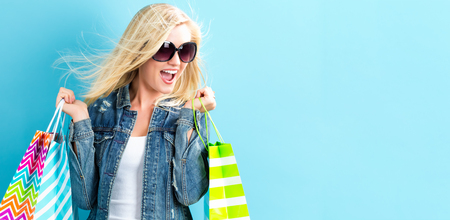 Photo for Happy young woman holding shopping bags on a blue background - Royalty Free Image