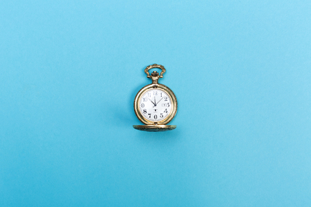 Foto de Small golden watch on a light blue background - Imagen libre de derechos