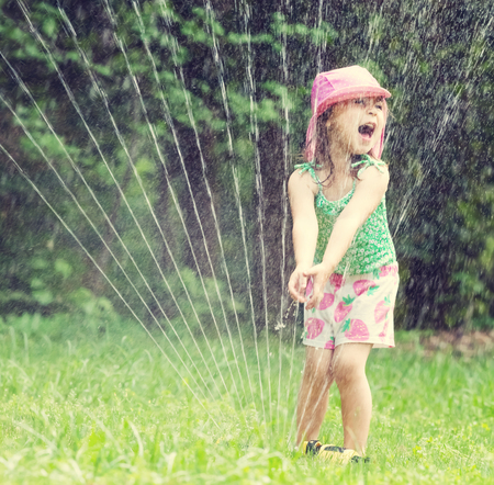 Photo pour Happy toddler girl playing in a sprinkler on a hot summer day - image libre de droit