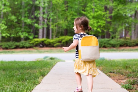 Photo for Toddler girl walking away from home on the sidewalk - Royalty Free Image