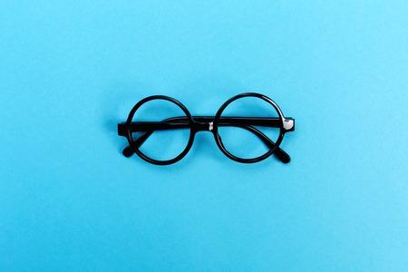 Photo pour A pair of round glasses on a bright blue background - image libre de droit