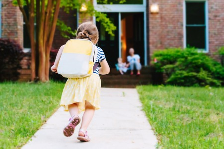Foto de Happy Toddler girl arriving home from school with a backpack - Imagen libre de derechos