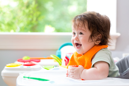Photo for Happy little baby boy with a big smile eating food - Royalty Free Image