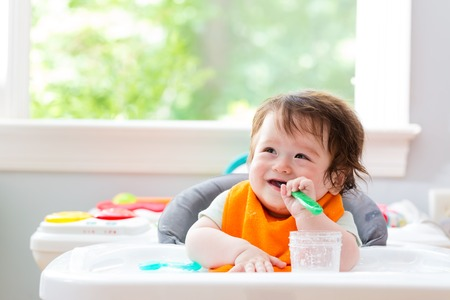 Photo pour Happy little baby boy eating food with a spoon - image libre de droit