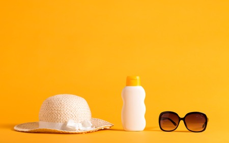 Foto de Summer sun protection objects theme on a yellow background - Imagen libre de derechos