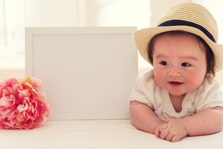 Photo for Happy baby boy with a white photo frame and a pink flower - Royalty Free Image