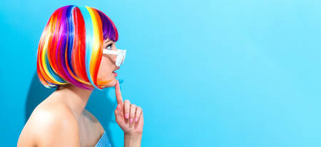 Foto de Beautiful woman in a colorful wig on a blue background - Imagen libre de derechos