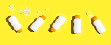 Foto de Sunscreen bottles arranged on a bright yellow background - Imagen libre de derechos