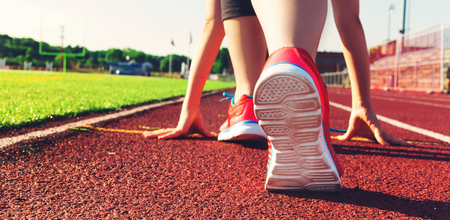 Photo for Female athlete on the starting line of a stadium track preparing for a run - Royalty Free Image