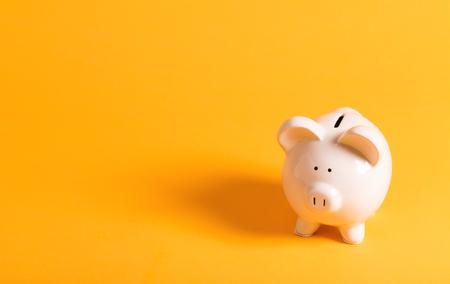 Foto de White piggy bank on yellow - Imagen libre de derechos