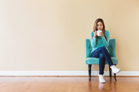 Photo for Young latina woman drinking coffee while sitting - Royalty Free Image