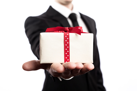 Photo pour Businessman presenting a gift box on a white backround - image libre de droit