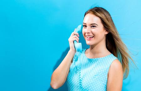 Photo pour Young woman talking on old fashioned phone - image libre de droit