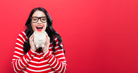 Photo pour Young woman with a piggy bank on a red background - image libre de droit