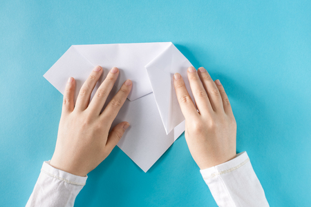 Photo for Persons hands folding a paper airplane on a blue background - Royalty Free Image