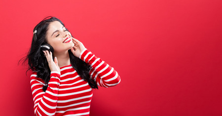 Photo for Happy young woman with headphones on a red background - Royalty Free Image