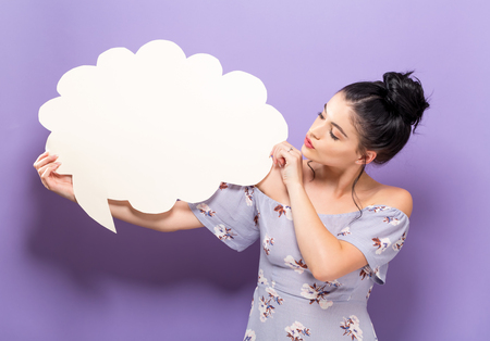 Foto de Young woman holding a speech bubble on a solid background - Imagen libre de derechos
