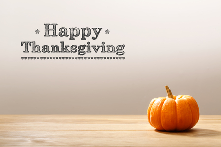 Foto de Thanksgiving message with a orange small pumpkin - Imagen libre de derechos