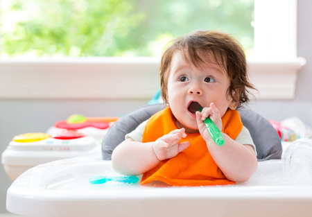 Photo for Happy little baby boy eating food with a spoon - Royalty Free Image