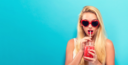 Foto de Happy young woman drinking smoothie on a solid background - Imagen libre de derechos