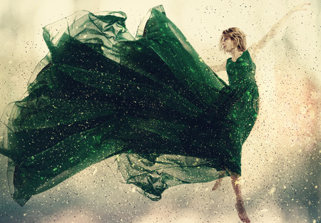 Photo for Beautiful woman in a green dress jumping - Royalty Free Image
