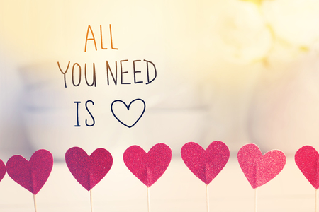 Foto de All You Need Is Love message with small red hearts with white dishes - Imagen libre de derechos