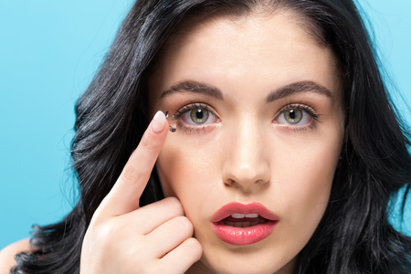 Foto de Beautiful young woman with contact lens on a solid background - Imagen libre de derechos