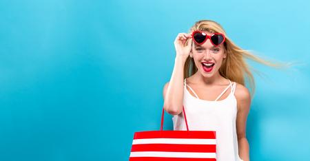 Foto de Young woman holding a shopping bag on a solid background - Imagen libre de derechos