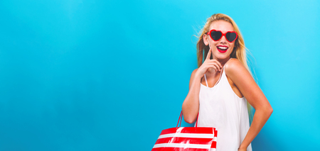 Photo for Young woman holding a shopping bag on a solid background - Royalty Free Image