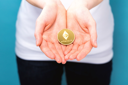 Photo for Woman holding a physical ethereum cryptocurrency coin in her hand - Royalty Free Image
