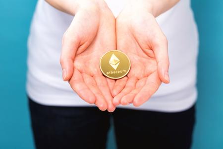 Foto de Woman holding a physical ethereum cryptocurrency coin in her hand - Imagen libre de derechos