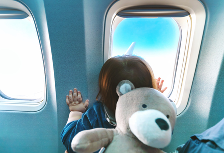 Foto de Little toddler boy looking out an airplane window while flying - Imagen libre de derechos