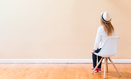 Photo for Young woman sitting in chair facing a big open wall - Royalty Free Image