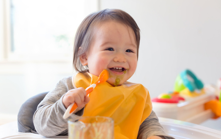 Photo pour Happy little baby boy eating food in his house - image libre de droit