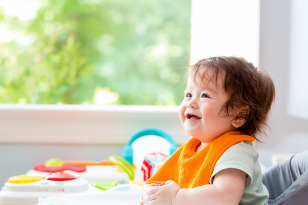 Photo pour Happy little baby boy with a big smile eating food - image libre de droit