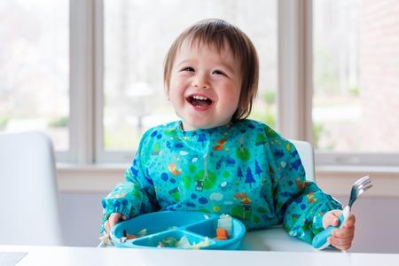 Photo pour Happy toddler boy with a big smile eating food - image libre de droit