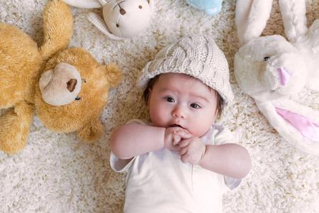 Photo pour Baby boy with his stuffed animals on a white carpet - image libre de droit