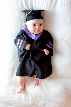 Photo for Little baby girl in graduation cap and gown - Royalty Free Image