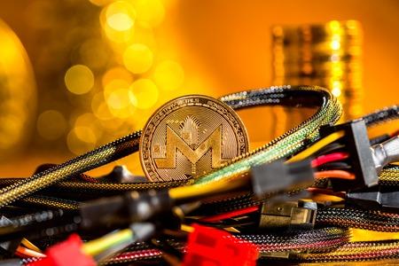 Foto de Monero cryptocurrency coin with compute wires on a golden background - Imagen libre de derechos